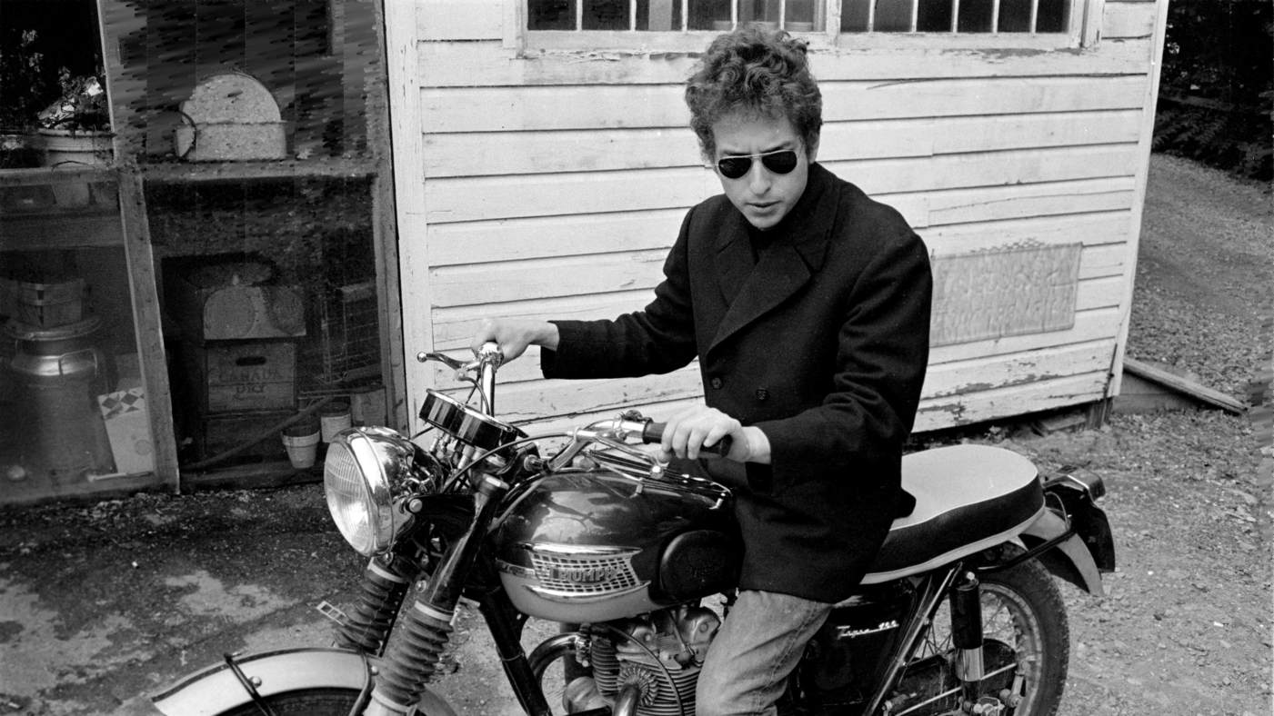 UNITED STATES - JANUARY 01: WOODSTOCK Photo of Bob DYLAN, sitting on motorbike wearing sunglasses, behind the Cafe at Woodstock (Photo by Douglas R. Gilbert/Redferns)